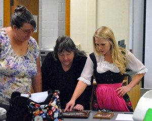 Jesse O. Walls | Contributor Molly Dyke (left), adult education and literacy (AEL) instructor, and Darlene Richards, general studies major, look at family photos brought in by ELI instructor, Rose Speck (right), showing her German heritage, during the last German class of the semester on April 28.